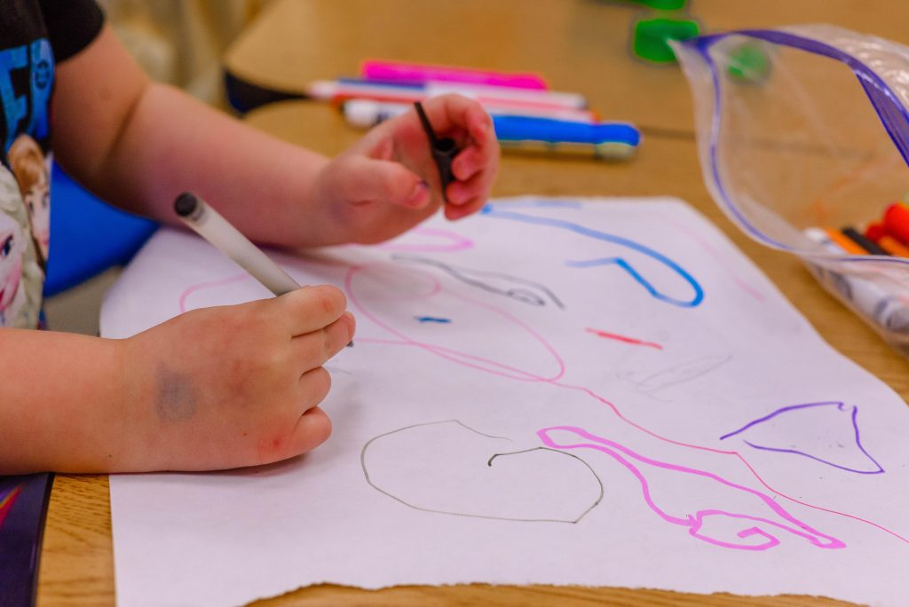 child's hands drawing on a large piece white paper