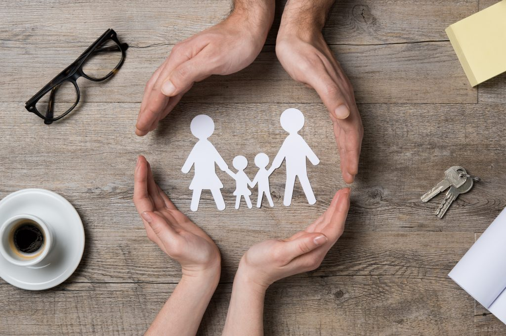 adult hands wrapping around image of a family